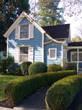 Victorian house entrance and garden. Beautiful Victorian style small house painted white and blue. Little grass, rose bush and other decorative plants in front Stock Photo