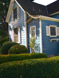 Victorian house entrance and garden. Beautiful Victorian style small house painted white and blue. Little grass, rose bush and other decorative plants in front Stock Image