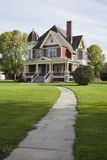Victorian house with lawn and sidewalk on sunny afternoon Stock Photos