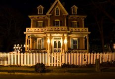 Victorian house at night. A somewhat spooky night view of a Victorian era house with a white picket fence in the foreground Royalty Free Stock Image