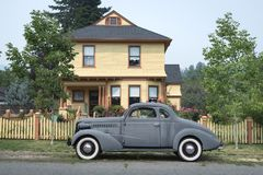 Victorian house with old car. Yellow victorian home with vintage car parked in front royalty free stock image