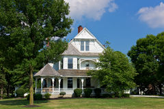 Victorian house with porch. White, three-story Victorian house with large porch and open lawn Royalty Free Stock Photography