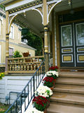 Victorian house with red and white flower pots. Victorian house brown color with stairs leading to porch and beautiful flower pots on the stairs Royalty Free Stock Images