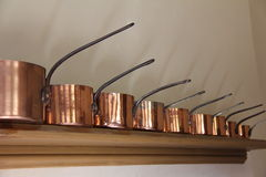Victorian Kitchen Copper Pots and Pans. Victorian Copper pots and pans on a shelf in an English Country House Royalty Free Stock Images