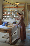 Victorian Kitchen maid - Cook preparing food .in authentic Victorian kitchen. Royalty Free Stock Images