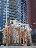 Victorian mansion nestled among modern apartment buildings in downtown Toronto. Laws to protect heritage architecture preserved this Victorian mansion nestled stock image