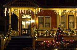 Victorian porch at Christmas. A night view of the porch of a lovely Victorian house decorated with many strings of lights for the Christmas holidays Royalty Free Stock Photography