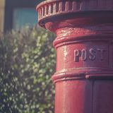 Traditional Red Pillar Box Post Drop in a Residential Street in. Victorian Red Letter Box for Mail Collection in a Residential Street in the UK Stock Images