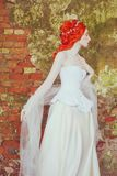 Victorian redhead princess with hairstyle in corset. Fabulous fairytale queen with historic hairdo against stone wall. Victorian d. Oll. Fantasy princess in royalty free stock images