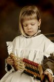 Victorian school-girl. Victorian style photo of a little girl counting with an abacus Royalty Free Stock Photography