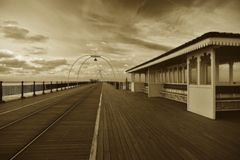 Victorian, seaside pier view. A victorian built, seaside pier and shelter. Photographed in a sepia style to give an aged retro look. This pier is located at Stock Photos
