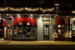 Victorian Storefront at Christmas. Street scene of a Victorian-Era storefront windows with Christmas decorations and old red awnings, lit up at night in Cape May Royalty Free Stock Photos