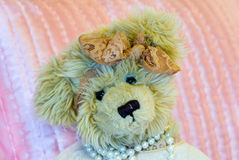 Victorian Teddy Bear. With Pink Lace Ribbon and Pearl Necklace, Against Pink Satin Pillow Royalty Free Stock Photos