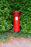 Victorian UK post pillar. An antique Victorian UK post pillar surrounded by green leaves Royalty Free Stock Image