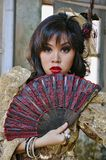 Victorian Woman. Chinese woman wearing victorian costume holding a fan, shoot at grunge building stock photo