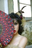 Victorian Woman. Chinese woman wearing victorian costume holding a fan, shoot at grunge building royalty free stock photo