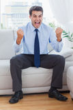 Victorious businessman cheering while sitting on sofa Stock Image