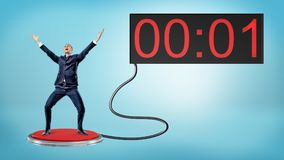 A victorious businessman on a large red push button connected to a screen with one remaining second. Just in time. Last chance. Corporate savior Stock Image