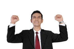 Victorious businessman raising his hands, isolated on white. Young Asian businessman looking up and expressing excitement of victory with both hands raised Stock Image
