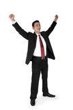 Victorious businessman standing. Full shot of attractive Asian businessman expressing victory, standing with both hands raised, isolated on white Royalty Free Stock Photo