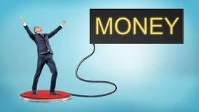A victorious businessman stands on a large red pushbutton that`s connected to a monitor with a word MONEY. Lottery winner. Luck and fortune. Business and Stock Photography