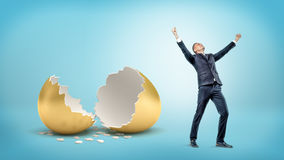 A victorious businessman stands near a large broken golden eggshell on blue background. stock images