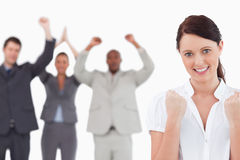 Victorious businesswoman with cheering team behind her Royalty Free Stock Photography