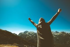 Victorious female person on mountain top. Victorious female person standing on mountain top with arms raised in V. Winning and success. Achievement and Royalty Free Stock Photos