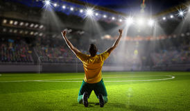 Victorious soccer player . Mixed media Royalty Free Stock Image