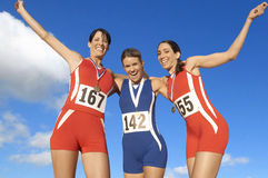 Victorious track athletes with arm around each other against sky stock photo