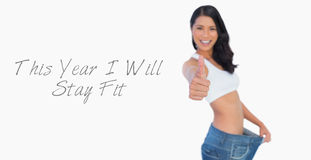 Victorious woman holding her too big pants thumbs up Royalty Free Stock Images