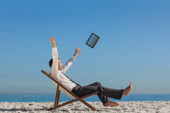 Victorious young businessman on his deck chair throwing his tabl Royalty Free Stock Photography