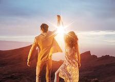 Victorious couple looking at the beautiful sunset. Victorious, young couple looking at the beautiful sunset Royalty Free Stock Photography