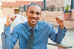 Victorious Young Professional Man. Portrait of an attractive, smiling, young, professional African American male raising his arms in a gesture of victory or Royalty Free Stock Image