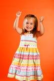 Victory. Cute little girl wearing sundress set against orange backdrop Royalty Free Stock Images