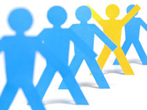 Victory. A yellow paper figure is celebrating between other blue paper figures Royalty Free Stock Image
