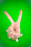 Victory. A victory sign made by a hand through a bright green paper Stock Image
