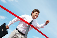 Victory. Photo of happy businessman crossing finish line during race Stock Image