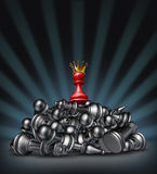 Victory. And the winner as a success concept with a red chess pawn wearing a gold crown on top of a mountain of defeated competitors that are lying down against Stock Photo