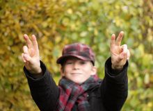 Victory. Boy making 'victory' gesture with his hands, selective focus on the hands Royalty Free Stock Photos