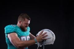 Victory Agressive American fotbollsspelare som skriker på hjälmen, medan stå mot svart bakgrund Royaltyfri Foto