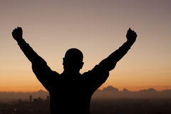 Victory Arms. Silhouette of man above city at sunrise with victorious arms royalty free stock photo