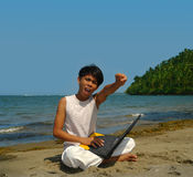 Victory on the beach. Asian boy with laptop computer on tropical pristine beach shouting victory. Concept of success and empowerment by education on a remote royalty free stock image