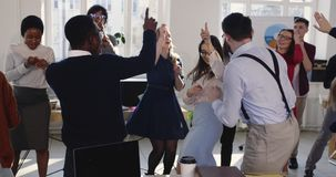 Victory celebration at healthy modern workplace. Excited young happy female boss dancing with multiethnic colleagues. stock footage