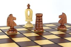 Victory in the chess game!. On the chessboard, two black horses and a boat of rooks announced a check and mat to the white king Stock Photography