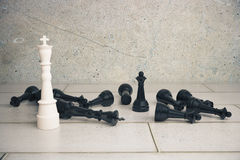 Victory concept with white chess king and black pawns  Royalty Free Stock Photos