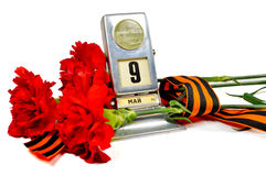 Victory Day concept isolated on white background - Vintage metal desk calendar with 9th May date and George ribbon with red carnat Royalty Free Stock Images