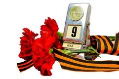 Victory Day-Konzept lokalisiert auf weißem Hintergrund - Weinlesemetalltischkalender mit am 9. Mai Datum und George-Band mit rote Lizenzfreie Stockfotografie