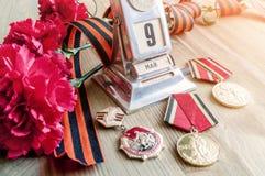 Victory Day-stilleven - de uitstekende kalender van het metaalbureau met 9 Mei-datum, medailles, George lint, rood anjersboeket Royalty-vrije Stock Foto