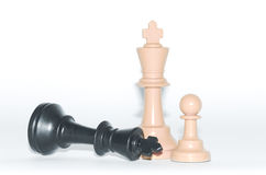 Victory - fallen black king, plastic chess pieces, white background Stock Image